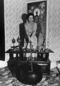 26 Sep 1964, London, England, UK --- Original caption: Against the backdrop of a painting of Isis, the Eqyptian mother goddess, Mrs. Eleanor Bone practices witchcraft in her London home, using traditional sword, cauldron, and assorted trinkets. She is one of the 5,000 practicing witches in Britain. --- Image by © Bettmann/CORBIS